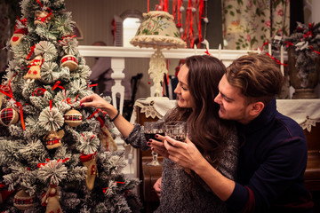 Beautiful couple sitting together, decorates a Christmas tree and drinking together. Cheers!