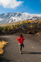 Mount Etna, Italy: panorama of the northern side of the volcano and a hiker walking on a lavic pathway
