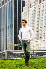Serious European businessman in New York. Wearing white shirt, blue jeans, brown boot shoes,  a young guy with beard, standing on green lawn in the front of business district, confidently looking up..