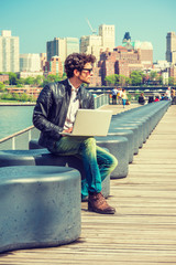 European businessman traveling, working in New York. Wearing black leather jacket, blue jeans, brown boot shoes, sunglasses, a guy with beard, sitting on bench at harbor, working on laptop computer..