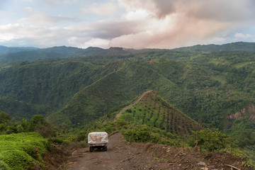 fruit truck crossing in the intricate hills with a beautiful view of the Colombian landscape