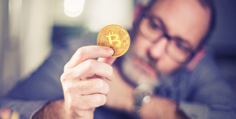 Bitcoin in hand of a businessman thinking about the future