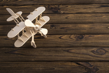 Wooden toy plane carved model on wooden old table. With a place for design