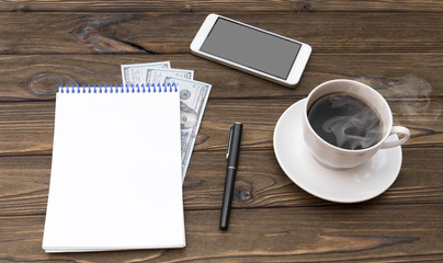 Cup of coffee, smartphone, dollars, notepad and pen on wooden desk.