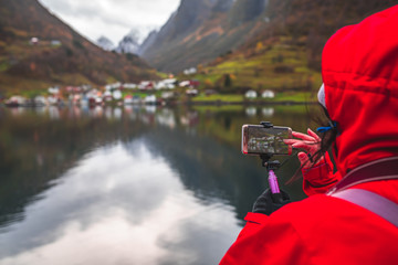 Tourist taking pictures of norwegian fjords on a smartphone