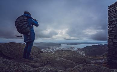 Backpacker tourist standing on the top of mount Ulriken