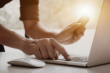 Online payment, Closeup image of man's hands holding a credit card and using laptop computer for online shopping with vintage filter tone