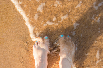 toes in the sand, with water