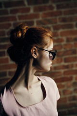portrait of a redhead girl on a brick wall background