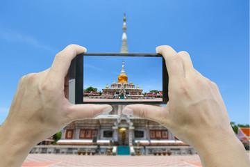 Girl taking pictures on mobile smart phone in Na Dun pagoda at Maha Sarakham in Thailand.