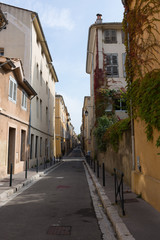Narrow Street with Stucco apartment buildings and metal posts separating the sidewalk and the street. Blue sky with thin clouds is above.