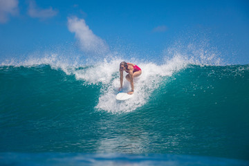 Indonesia, Bali, July 23 2016: A female surfer, Leonor Fragoso riding big blue ocean surfing wave, shot from water level