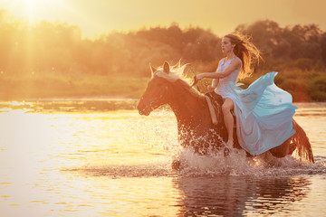 Female horse rider running through water with splashes at sunset background