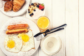 Breakfast of sunny side up eggs, sausages, orange juice, and fruits on whitw wooden background, top view