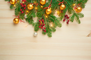 Christmas background decoration with berries, balls, and fir tree branches flat lay on wooden texture. Top view with blank space.