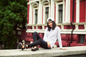 Young woman in casual clothes posing on a city street .The concept of easy casual wear .
