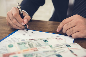 Businessman signing agreement contract paper with money, Russian ruble banknotes, on the table