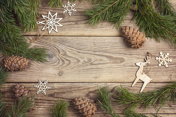 Frame made of pine branches and Christmas decorations rustic elements on old wooden board. Copy space, top view.