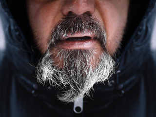 Mann mit grau schwarz eingefrohrenem Bart dick eingepackt in Jacke in kälte im Winter