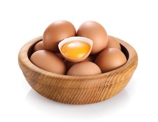Wooden bowl with eggs isolated on white background. Broken egg, yolk.