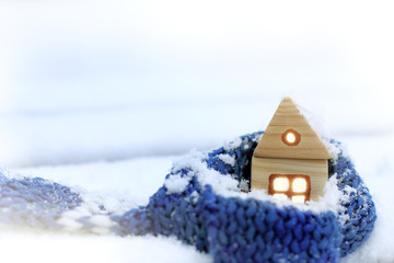 warming technology for winter/ wooden house wrapped in a blue scarf in the middle of snowdrifts