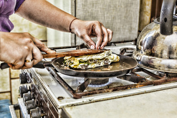 A woman is preparing breakfast at home in the kitchen. Toasts in a frying pan with egg green and bacon. Healthy food.