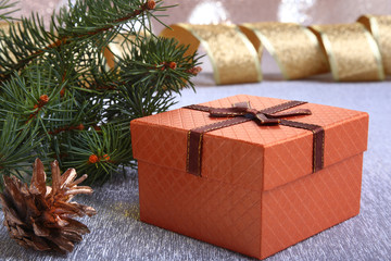 Christmas decoration with gift boxes, christmas tree and cones on a blurry, sparkling and fabulous background.