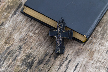 Christian Cross and Holy Bible on old wooden table