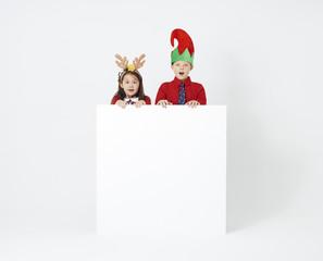 Surprised siblings with banner at studio shot