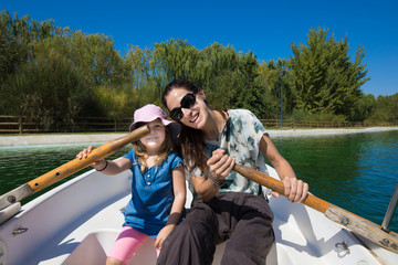 Four years old blonde girl with hat with woman mother sitting in boat, posing smiling happy, paddling at park lake