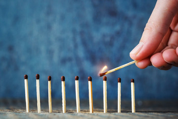 A lit match in hand tries to set another match on fire. The conc