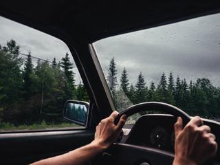 roadtrip moment im inneren eines autos mit händen am lenkrad halb offenem fenster in waldumgebung und regen