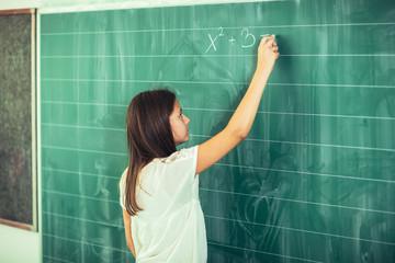 Happy schoolchild writing on blackboard with chalk