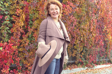 Very happy woman walks in the autumn day.
