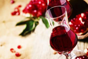 Pomegranate liqueur, vintage wooden background, selective focus