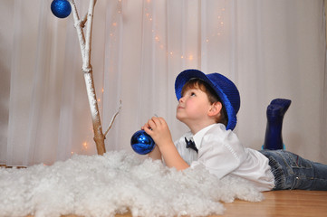 Child with blue hat wait a New Year. Nice little boy and New Year's decoration