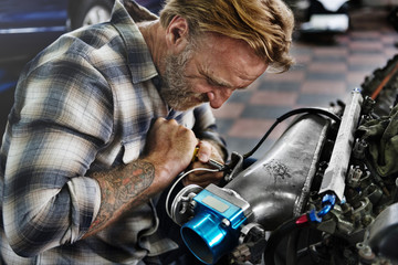 A mechanic fixing an engine