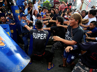 Activists scuffle with members of the Civil Disturbance Management police during a protest action against President Rodrigo Duterte's plan to set up a Revolutionary Government, along a street in metro Manila