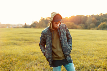 Handsome man with a cap in a military jacket with a hoodie on the nature at sunset