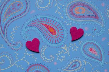 2 pink Herzen auf Hintergrund aus hellblauem Paisley Muster