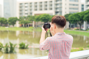 Half length of young asian man outdoor in the city taking picture