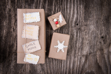 New Year resolutions and handmade gift boxes on rustic wood