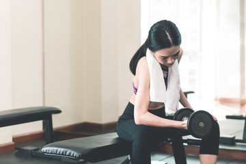 Small thin asian woman is lifting dumbbell in fitness club