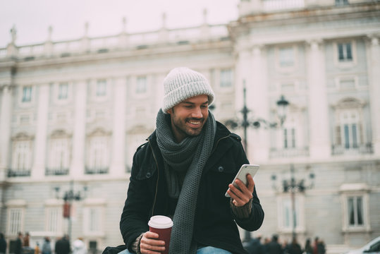 Young blonde man on the mobile phone and drinking coffee near the royal palace in winter  .