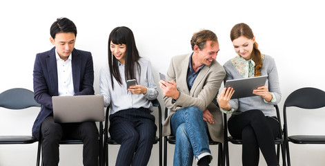 Sitting men and women using various mobile devices.