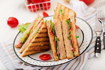 Club sandwich - panini with ham, cheese, tomato and herbs.
