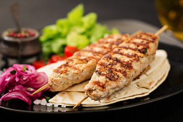 Minced Lula kebab grilled turkey (chicken) with fresh vegetables.