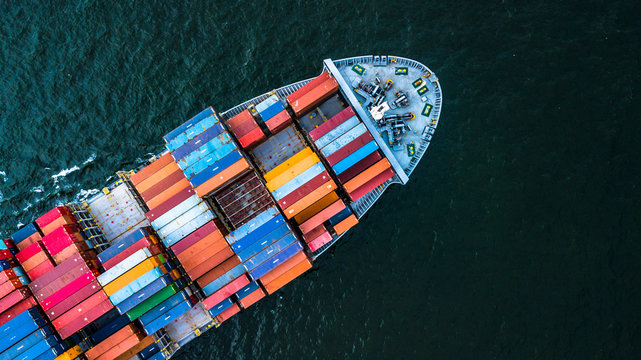 Aerial view from drone, Container cargo ship in import export business logistic and transportation of international by container cargo ship in the open sea in Asia.
