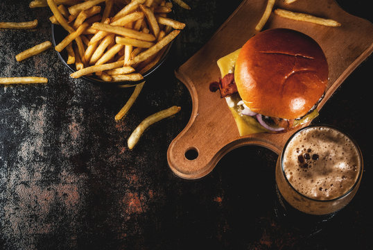 Fresh meat and cheese burger with French fries and glass of dark ginger beer, on dark blue background, copy space top view