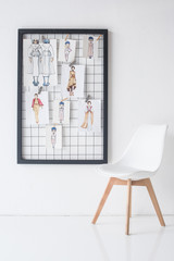 black frame with sketches on wall and chair in white room